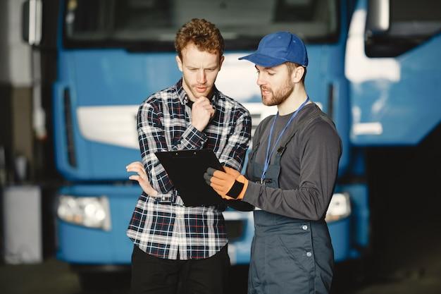 Due ragazzi che parlano di lavoro. lavora in garage vicino al camion. trasferimento di documenti con merci