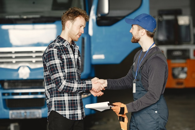 Two guys talking about work. work in garage near truck. transfer of documents with goods