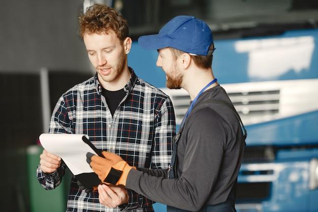 仕事について話している2人の男。トラックの近くのガレージで作業します。商品を含む伝票の転送