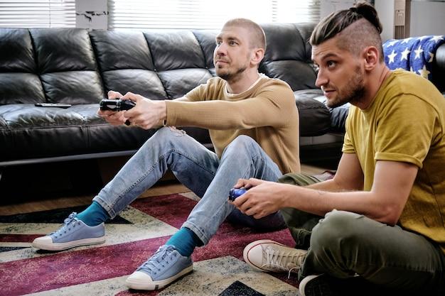 거실 바닥에서 비디오 게임을 하고 있는 조이스틱을 가진 두 남자