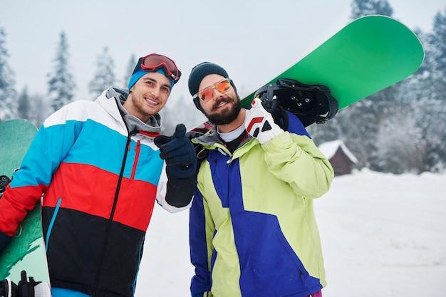 冬休み中にスノーボードを持った2人の男