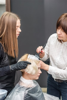 Two hairdressers are dyeing hair of woman