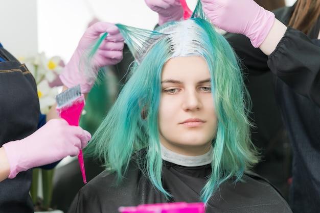 Два парикмахера используют розовую щетку при нанесении краски на волосы во время процесса обесцвечивания корней волос.