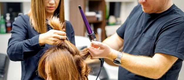Two hairstylists using a curling iron on customers long brown hair in a beauty salon