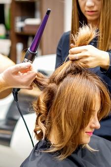 Два парикмахера используют щипцы для завивки длинных каштановых волос клиентов в салоне красоты
