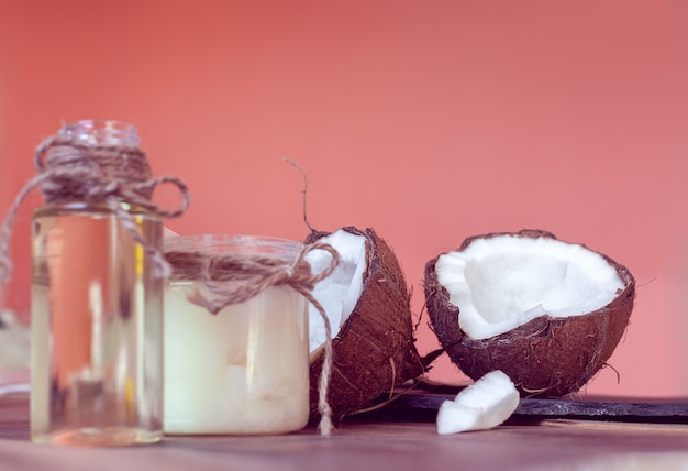 Two half of coconut and coconut oil in a bottles