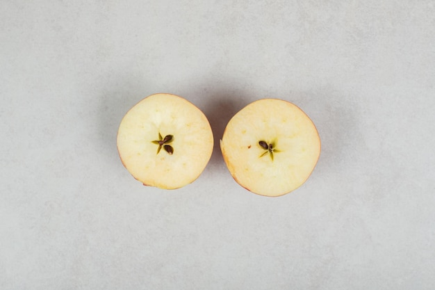 Two half cut red apples on gray surface