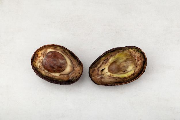 石の表面に半分腐った甘やかされて育ったアボカド2つ不適切な食料貯蔵有機性廃棄物の削減