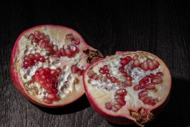 Two halfs of ripe pomegranate on a dark background,