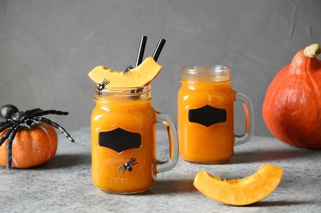 Два коктейля из тыквы на хэллоуин или сок, специи, украшенные морковью пауки для праздничной вечеринки