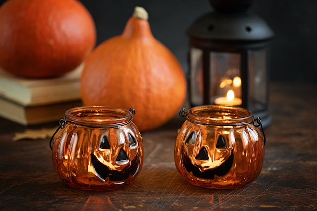 Two halloween pumpkins head jack glass lantern. halloween decoration on wooden table background, selective focus - image