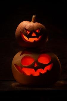 Две тыквы на хэллоуин со страшным лицом в темноте
