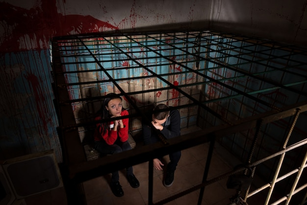 Two halloween victims imprisoned in a metal cage with a blood splattered wall behind them sitting in terror awaiting their fate
