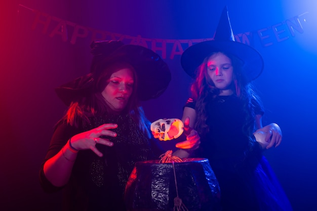 Two halloween witches making a potion and conjure in halloween night magic holidays and mystic