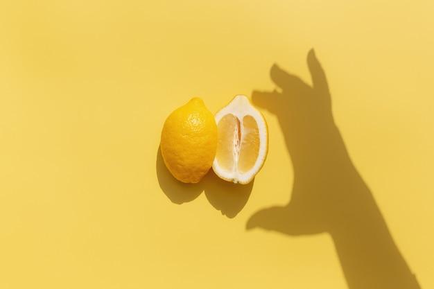黄色の表面に手からの影とレモンの2つの半分のカット