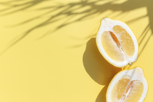 黄色の背景にヤシの葉からの影とレモンの2つの半分のカット。健康的な食事、旅行または休暇の概念