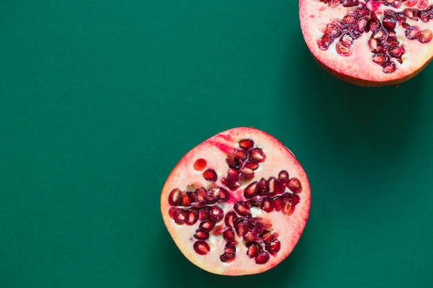 Two halved pomegranate on green background