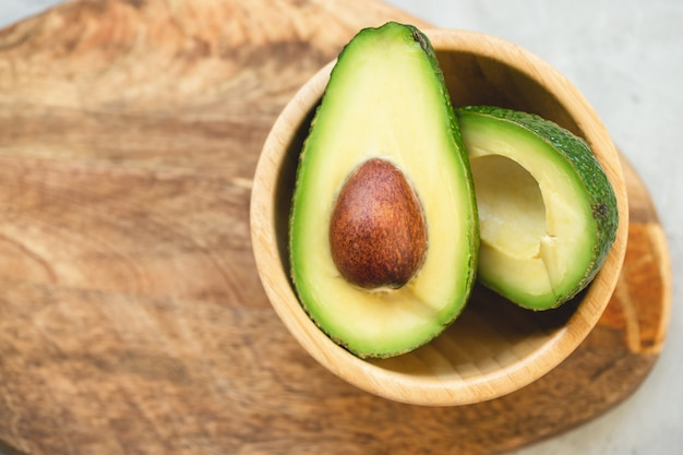 Two halves of avocado in a bowl on a wooden board