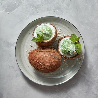 Two halves of coconut with homemade green mint ice cream and whole coconut on a plate on a gray table, copy space.. summer concept.
