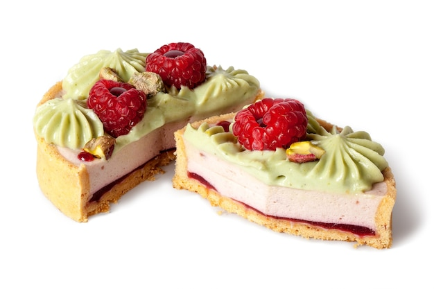 Two halves of dessert basket with pistachios cream decorated with raspberries