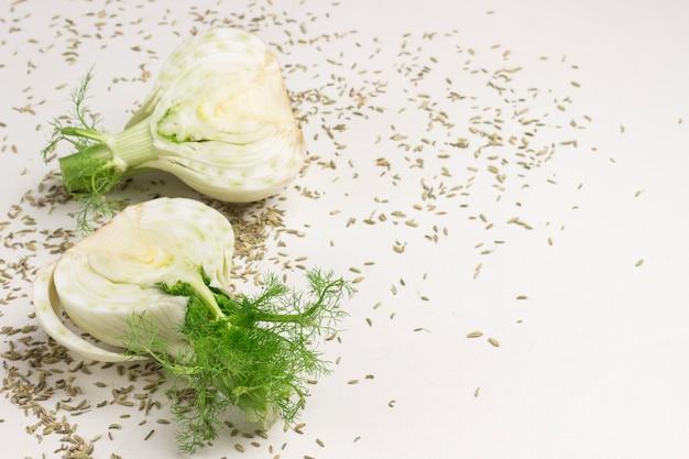 フェンネルの球根の2つの半分、テーブルの上のフェンネルの種子。健康食品