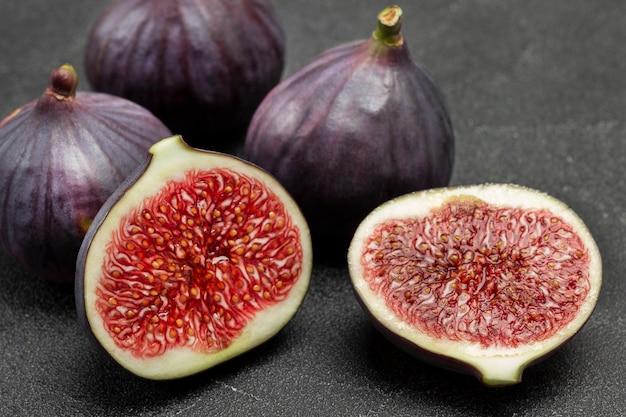 イチジクの2つの半分と全体の紫色のイチジク。熟した果肉。閉じる。黒の背景。