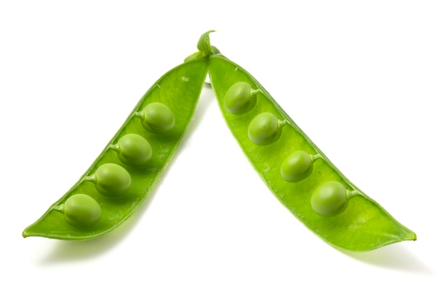 Две половинки зеленого молодого горошка, изолированные на белом фоне. стручки бобовых, сытный и вкусный горох.