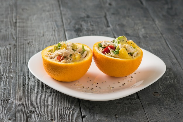 Две половинки апельсина с салатом из авокадо и курицей на белой тарелке на деревянном столе. диетическое питание из тропических фруктов и курицы.