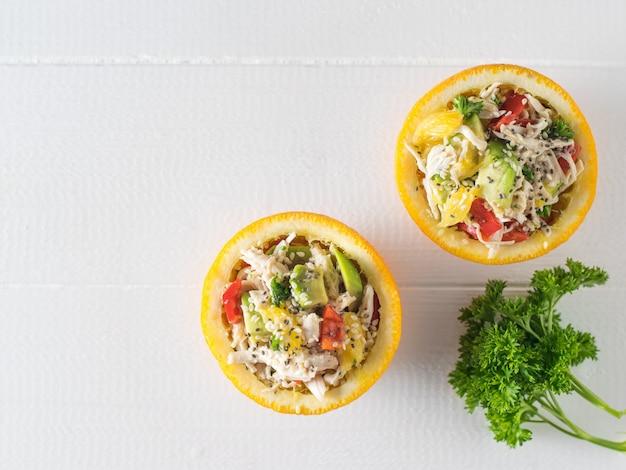 Две половинки апельсина с куриным салатом и авокадо на белом деревянном столе. диетическое питание из тропических фруктов и курицы.