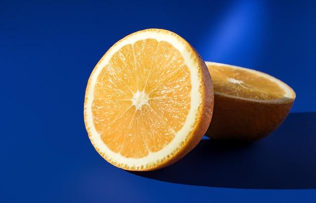 밝은 햇빛에 파란색 배경에 익은 오렌지의 두 반쪽.