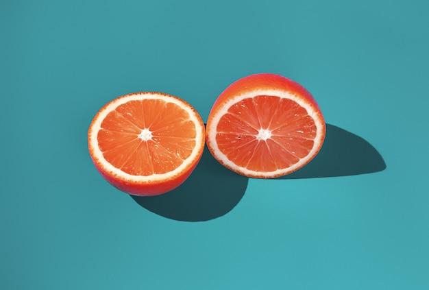 밝은 햇빛에 녹색 배경에 익은 오렌지의 두 반쪽.