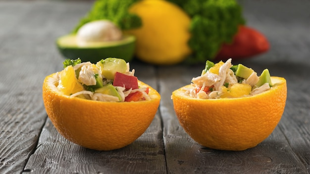 The two halves of the oranges with chicken salad and avocado. diet food of tropical fruits and chicken.