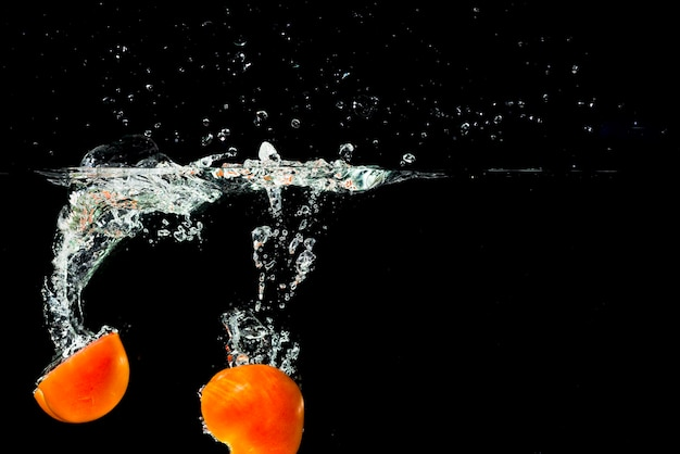 Two halves tomatoes falling into clean water with splash