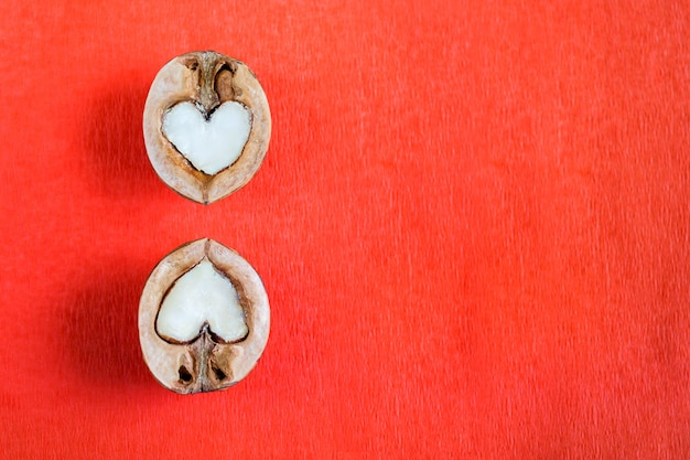 Two halves of walnut in shape of heart are lying over one another on red textured paper background.