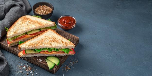 紺色の背景の木の板に2つのハムとチーズのサンドイッチ。側面図、コピースペース