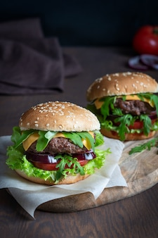 Два гамбургера из говяжьего мяса, салатного сыра и нарезанной булочки, поданные на темном деревянном столе