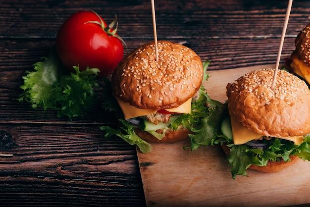 ボード上の肉、チーズ、サラダ、トマトの2つのハンバーガー