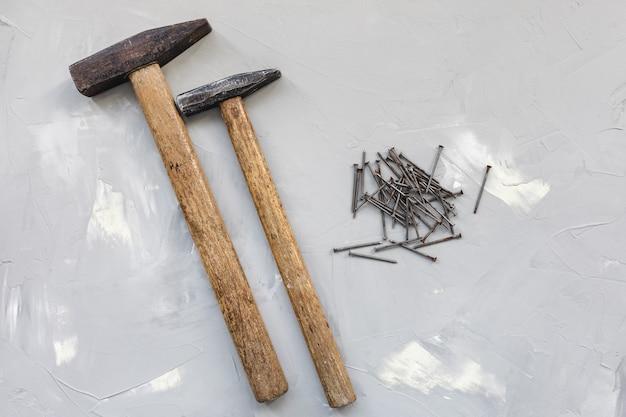 2つのハンマーと灰色の表面に古いさびた釘