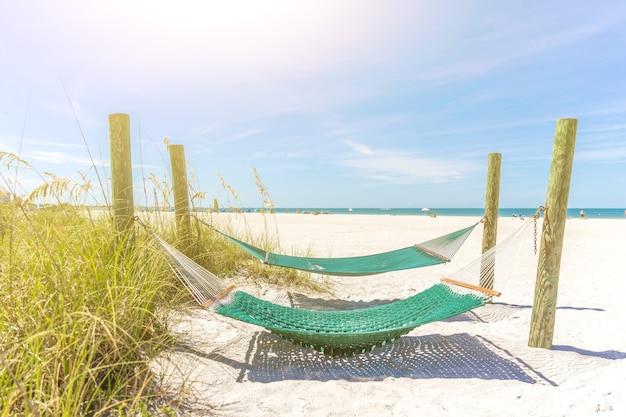 太陽の光が差し込む美しい空のビーチにある2つのハンモック