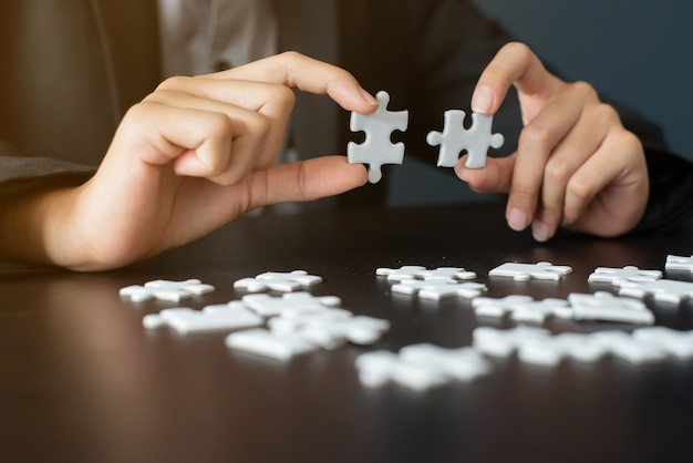 Two hand completing white jigsaw