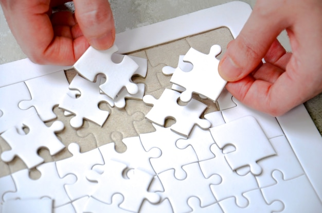 Two hand holding a piece of white jigsaw incomplete puzzle on the table
