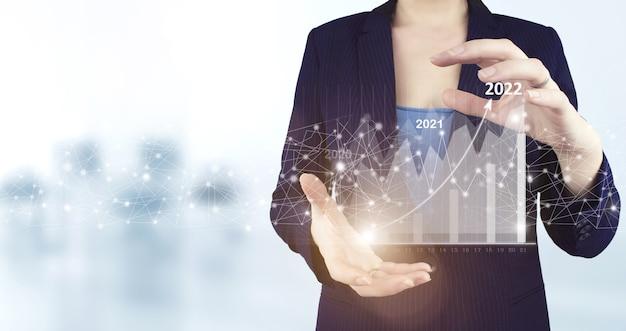 밝은 배경이 있는 가상 홀로그램 성장 그래프 차트 아이콘을 들고 있는 두 손. 개념은 2022년 새해를 시작합니다. 그의 사업에서 긍정적인 지표의 성장과 증가를 계획하십시오.