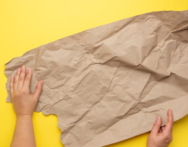 Two hand holds piece of crumpled brown paper on a yellow background, element for designer, top view