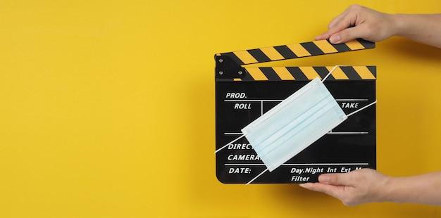 Two handは、フェイスマスク付きの黒いカチンコまたは映画のスレートを持っています。黄色の背景でビデオ制作や映画産業で使用されます。
