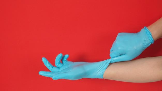 両手は、赤い背景に青いラテックス手袋を着用して引っ張っています。