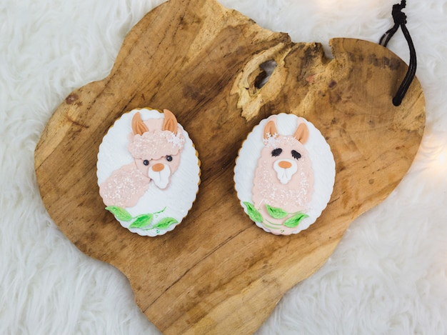 Two hand painted gingerbreads on a wooden . the cute llama shaped are painted on the gingerbread. close-up.