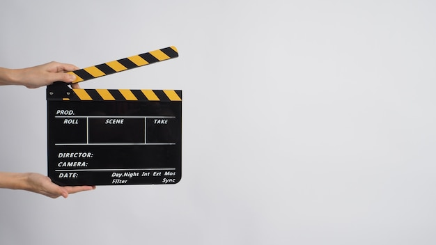 Two hand's holding black with yellow clapper board on white background.