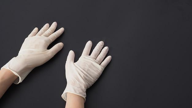 両手は白いラテックス手袋を着用し、黒い背景に手をつないでください。