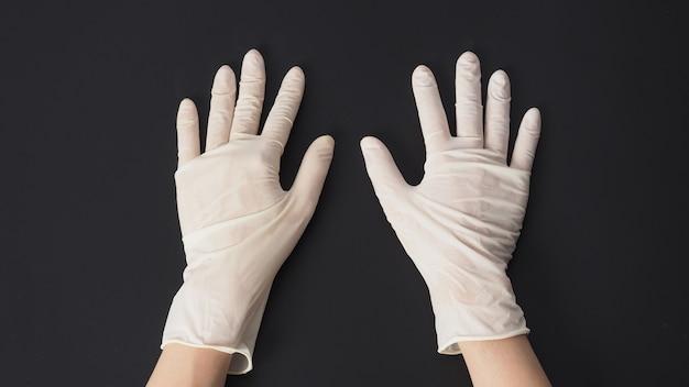 両手は黒い背景に白いラテックス手袋を着用します。