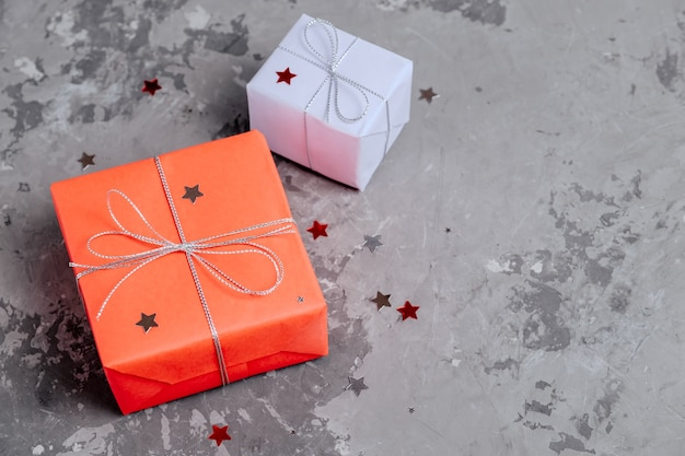 Two handcrafted festive presents wrapped in red and lilac paper